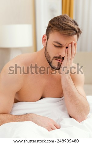 Early wake up. Depressed young man sitting in bed and touching face with hand