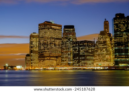 Early winter evening and the New York City Skyline at sunset showing the lower manhattan area and wall street  - stock photo