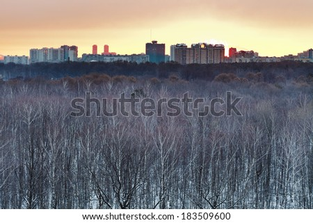 Early yellow dawn over snowy city park in spring - stock photo