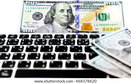 Earning,income money from the internet and social network with American dollar currency put on keyboard of notebook,computer isolated on white background,Focus on eye of franklin on first banknote