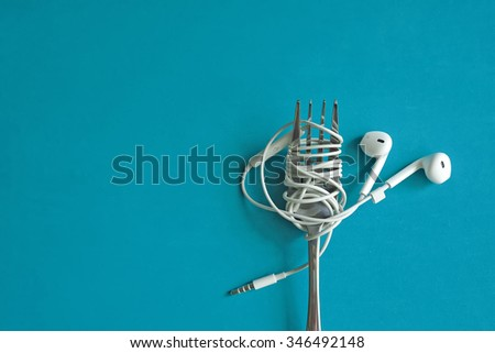 Earphones on fork on blue background. Concept of Music. - stock photo