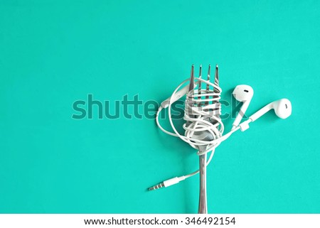 Earphones on fork on mint green background. Concept of Music. Bright color style. - stock photo