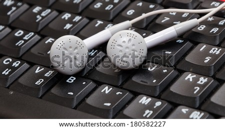 Earphones on keyboard thai and english