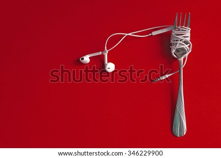 Earphones on metal fork. Concept of Music. - stock photo