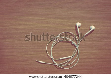 Earphones on Wooden Background, Vintage color tone - stock photo