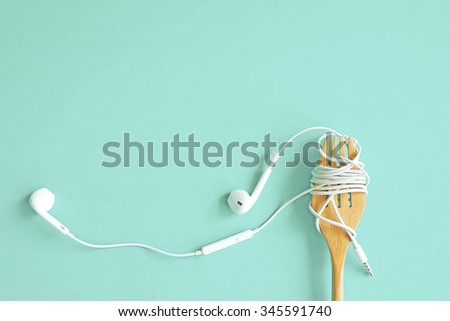 Earphones on wooden fork. Concept of Music. Pastel tone. - stock photo