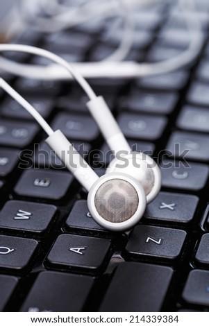 Earphones over laptop keyboard - stock photo