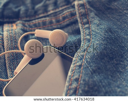 earphones with mobile smartphone in the pocket old jeans in vintage style - stock photo