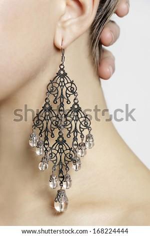 Earring on woman's ear. - stock photo