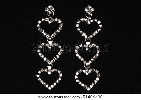 earrings in the form of hearts with precious stones on a black background - stock photo