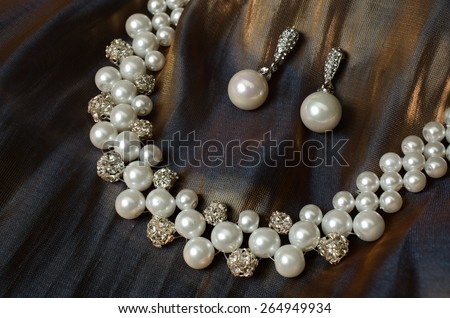 earrings with a necklace on a fabric - stock photo