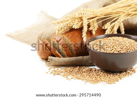 Ears of wheat and bowl of wheat grains on white background - stock photo