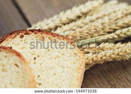 Ears of wheat and bread on the wooden table. Small depth of field.