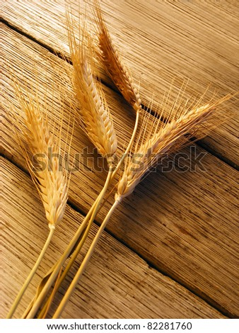 Ears of wheat on a wood background. Soft light - stock photo
