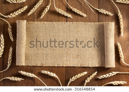 ears of wheat on wooden background - stock photo