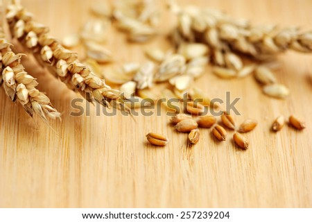 Ears of wheat on wooden board - stock photo