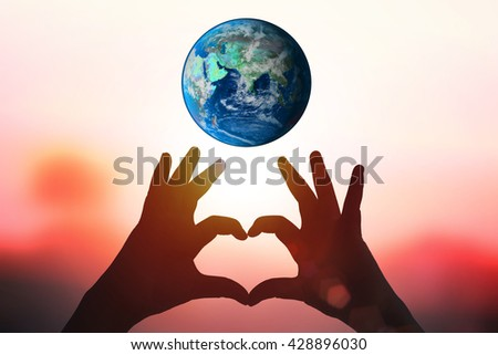 earth and hands under a heart-shaped Silhouette .Natural background blurring.warm colors and bright sun light.Earth day holiday concept. Elements of this image furnished by NASA - stock photo