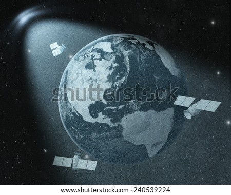 Earth and orbiting satellites drawing  in spot of light. Elements of this image furnished by NASA  - stock photo
