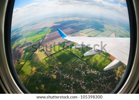 earth and plane wing view from an illuminator - stock photo