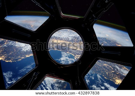 Earth and star in spaceship window porthole. Elements of this image furnished by NASA - stock photo