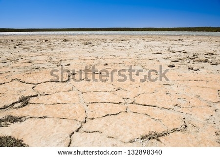 Earth badly cracked and broken under a hot sky - stock photo