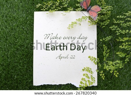 Earth Day, April 22, Concept with recycled paper in grass with fern and butterfly and text. - stock photo