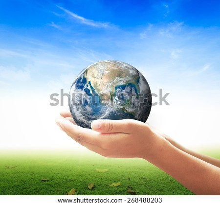 Earth day concept: Human hands holding globe over nature background. Elements of this image furnished by NASA.