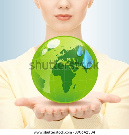 earth day, people, ecology and environment concept - close up of woman holding green globe in her hands - stock photo
