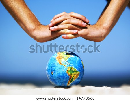 Earth globe on the beach and hands over it. Ideal for Earth protection concepts, recycling, world issues, enviroment themes