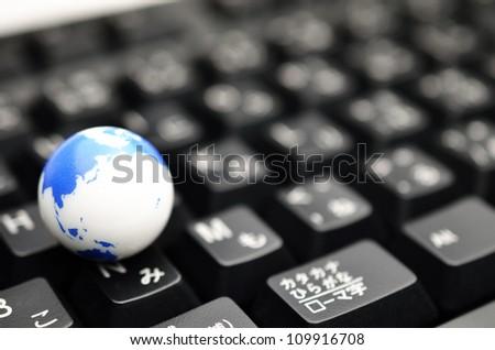 Earth globe over keyboards - stock photo