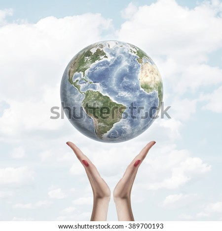 Earth in air over hands on background of sky and clouds. Environmental protection concept , care for planet