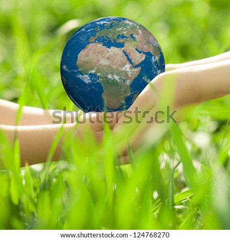 Earth in children`s hands against green grass blurred background. Elements of this image furnished by NASA