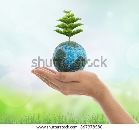 Earth in hand with natural light background. Environment and ecology concept. - stock photo