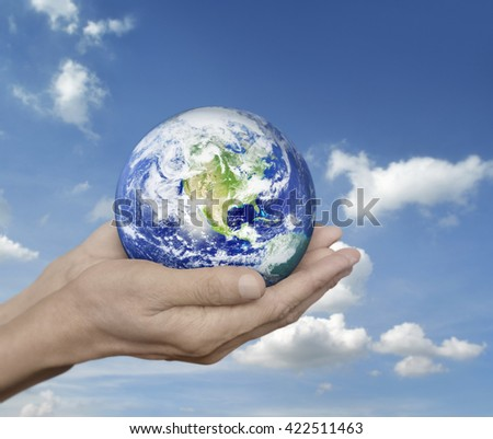 Earth in hands over blue sky with white clouds, Environment concept, Elements of this image furnished by NASA