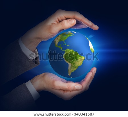Earth in human hands on the black background. Elements of this image furnished by NASA