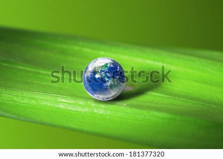 Earth in water drop reflection on green leaf, Elements of this image furnished by NASA - stock photo