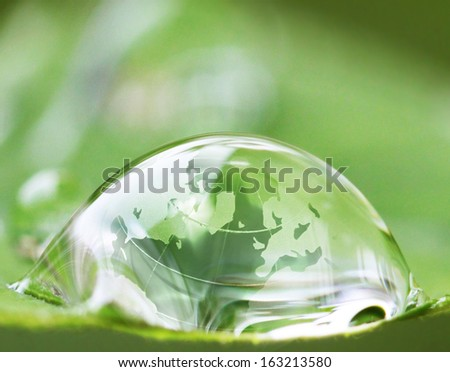 earth in waterdrop reflection on green leaf  - stock photo