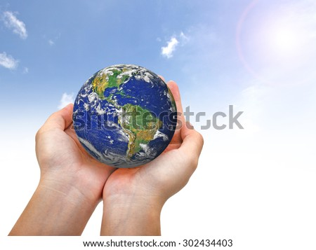 Earth planet in female hand and blue sky - Elements of this image furnished by NASA