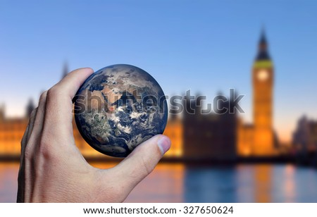 Earth planet in male hand. London city background. Elements of this image furnished by NASA - stock photo