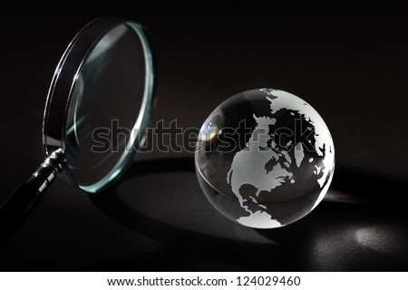 Earth with magnifying glass and light beam - stock photo