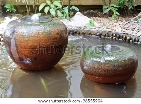 Earthenware fountain jar in the garden of building. - stock photo