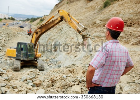 Earthmoving works. engineer builder watching construction machinery with hydrohammer
