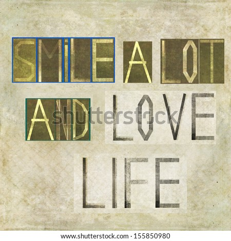 """Earthy background image and design element depicting the word """"Smile a lot and love life"""" - stock photo"""