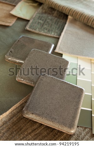 Earthy green & brown interior design plan with fabric and paint color swatches, and ceramic tiles. - stock photo