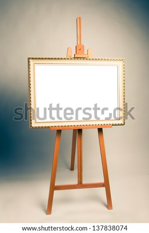 easel with antique painting frame, cross-processed image - stock photo