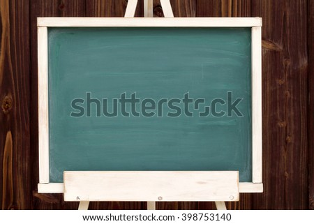 easel with blank chalkboard on a wood wall background - stock photo