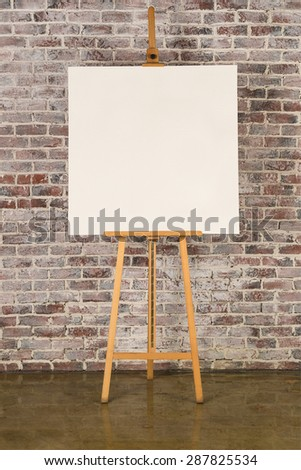Easel with blank square canvas on a brick wall background - stock photo