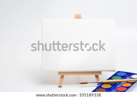 easel with brush and water colors isolated white - stock photo