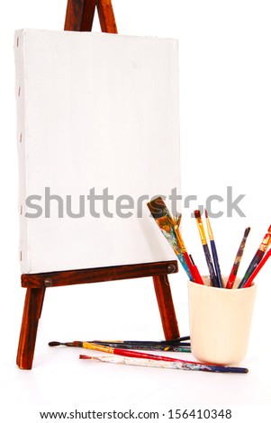 Easel with brushes - stock photo