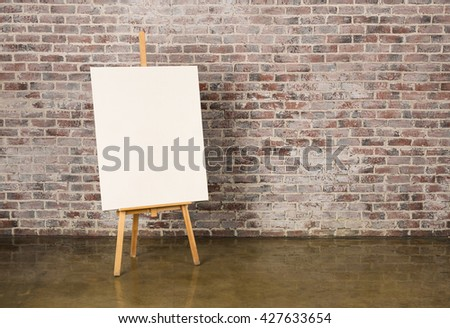 Easel with canvas on a grunge brick wall background - stock photo